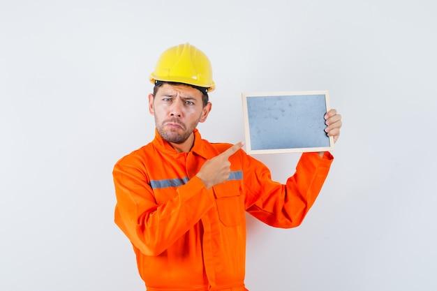 Jonge werknemer wijzend op schoolbord in uniform, helm.