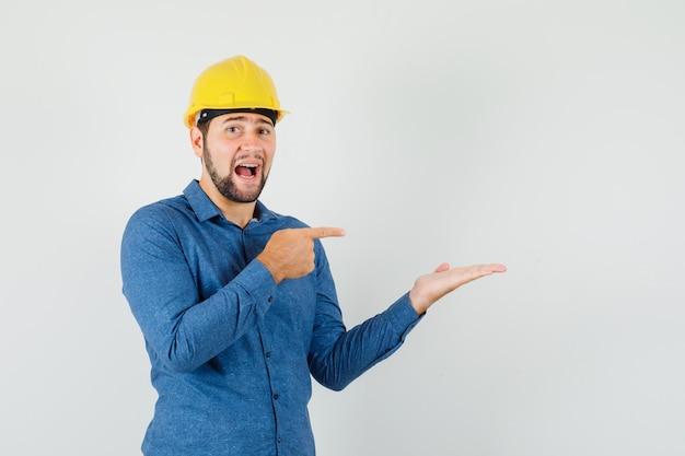 Jonge werknemer wijzend op zijn handpalm opzij gespreid in shirt, helm en opgewonden kijken.