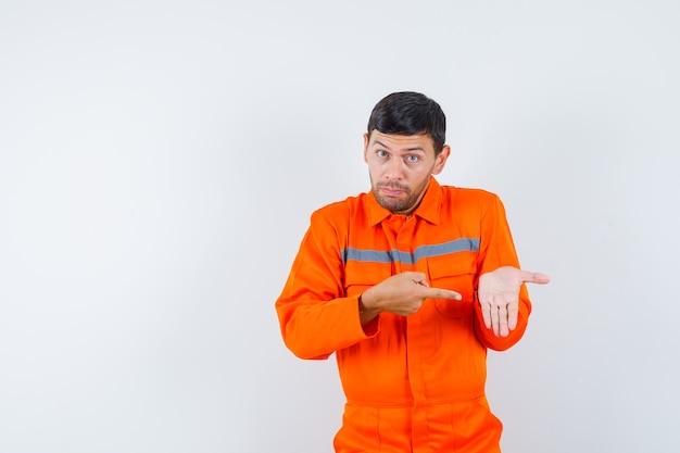 Jonge werknemer wijzend op zijn lege handpalm in uniform.