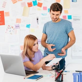 Jonge werknemers die geschrift op notitieboekje analyseren dichtbij werkplaats