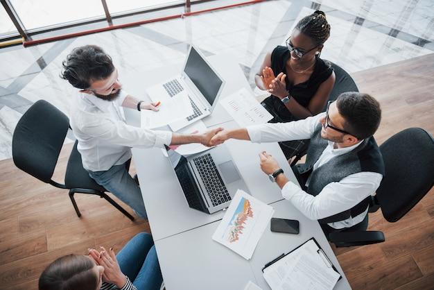 Jonge werknemers die in het bureau bij de lijst zitten en laptop, een concept van de de brainstormingsvergadering van het teamwerk met behulp van.