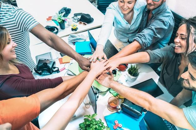 Jonge werknemers startarbeiders die handen stapelen bij stedelijke studiowerkruimte op brainstormingsproject