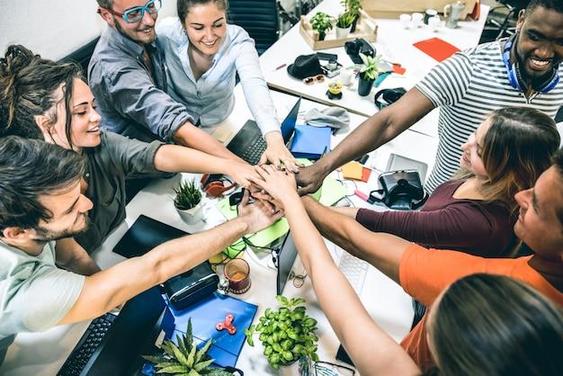 Jonge werknemers startarbeiders die handen stapelen bij studio op het project van de ondernemerschapbrainstorming