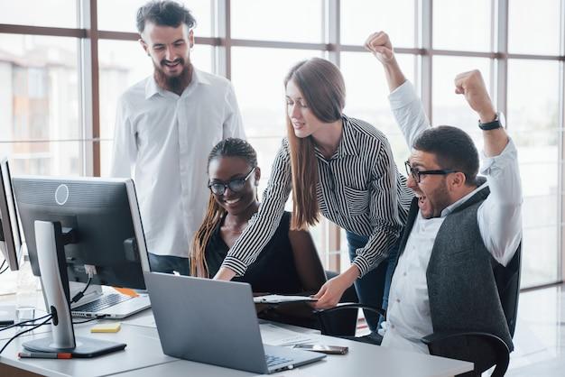 Jonge werknemers zitten in het kantoor aan de tafel en het gebruik van een laptop
