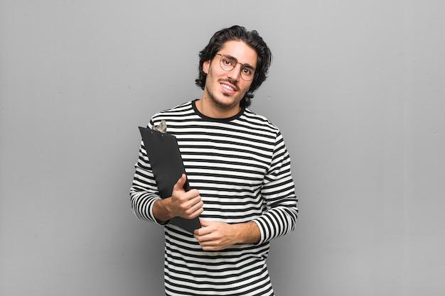Jonge werknemersmens die een inventaris gelukkig, glimlachend en vrolijk houdt.