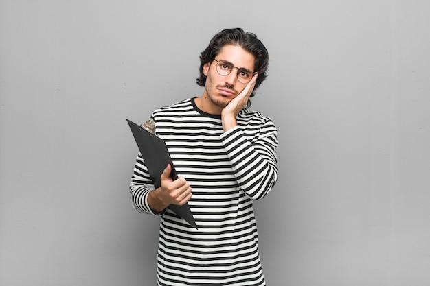 Jonge werknemersmens die een inventaris houdt die zich verveelt, vermoeid en een relaxdag nodig heeft.