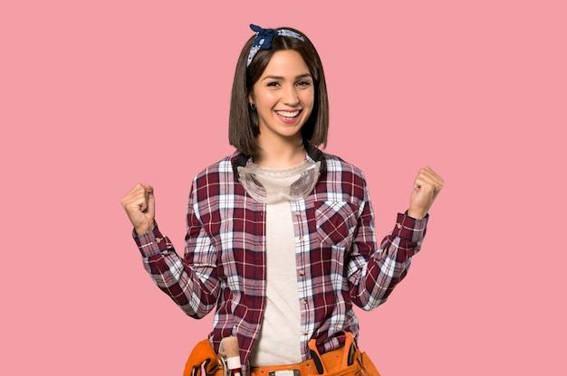 Jonge werknemersvrouw die een overwinning op geïsoleerde roze muur viert