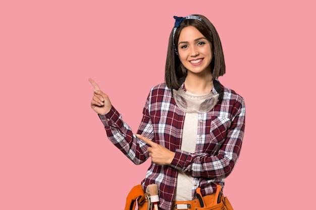 Jonge werknemersvrouw die vinger richten aan de kant op geïsoleerde roze muur