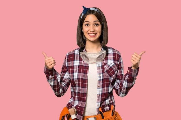 Jonge werknemersvrouw met omhoog duimen omdat iets goeds op geïsoleerde roze muur is gebeurd