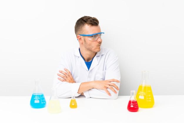 Jonge wetenschappelijk met veel laboratoriumfles die een idee denkt