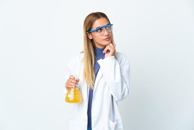 Jonge wetenschappelijke vrouw die op witte muur wordt geïsoleerd en omhoog wordt gekeken