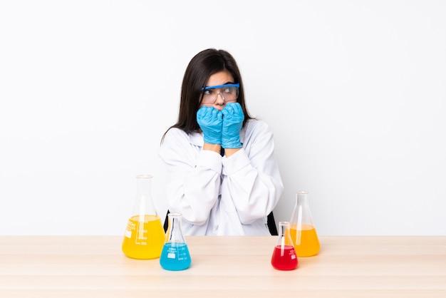 Jonge wetenschappelijke vrouw in een tafel nerveus en bang handen naar mond brengen