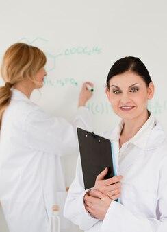 Jonge wetenschapper die een formule schrijft, geholpen door haar assistent