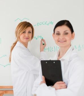 Jonge wetenschapper die een formule schrijft, geholpen door haar vrouwelijke assistent