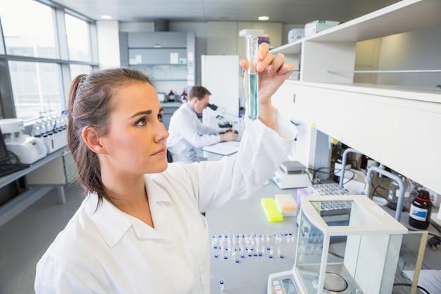 Jonge wetenschapper die reageerbuis steunt