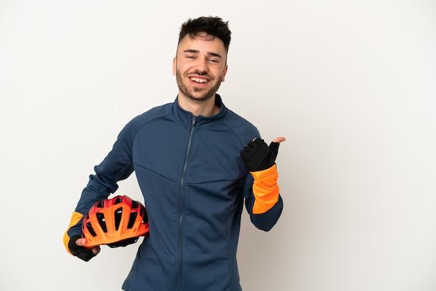 Jonge wielrenner geïsoleerd op een witte achtergrond die naar de zijkant wijst om een product te presenteren