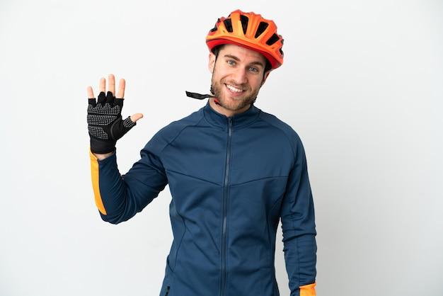 Jonge wielrenner man geïsoleerd op een witte achtergrond die met de hand salueert met een gelukkige uitdrukking
