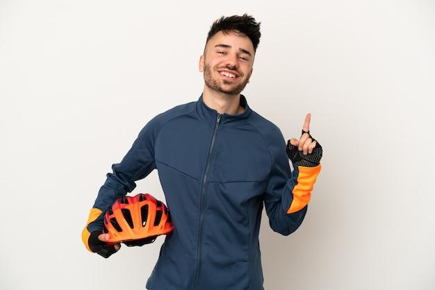 Jonge wielrenner man geïsoleerd op een witte achtergrond tonen en optillen van een vinger in teken van de best