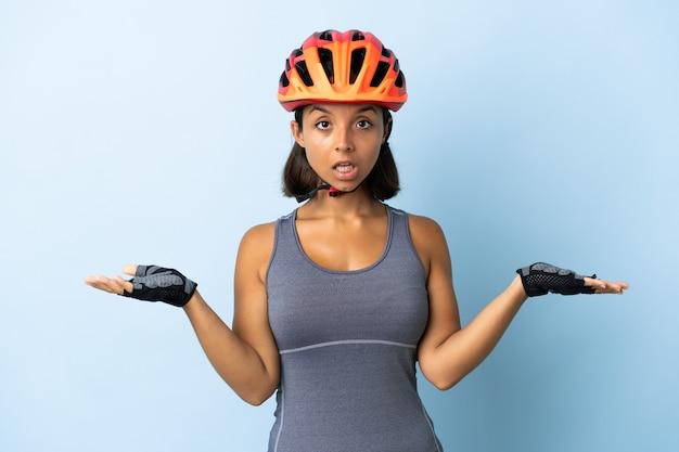 Jonge wielrenner vrouw geïsoleerd op blauw met geschokt gelaatsuitdrukking