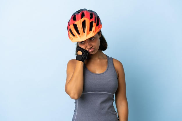 Jonge wielrenner vrouw geïsoleerd op blauw met vermoeide en verveelde uitdrukking