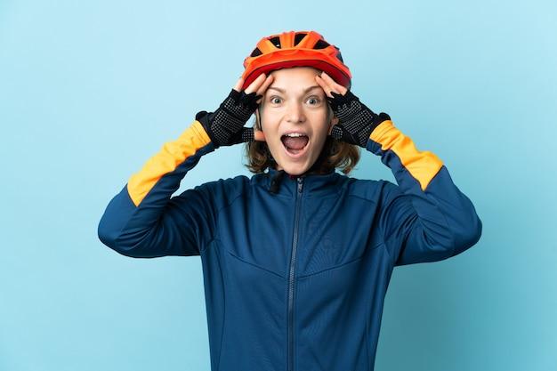 Jonge wielrenner vrouw geïsoleerd op blauwe achtergrond met verrassing expression