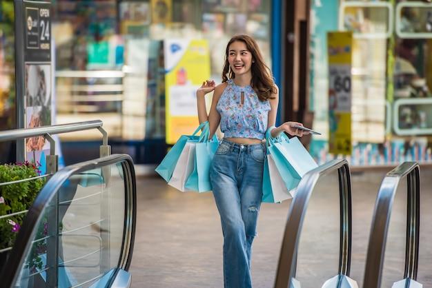Jonge winkelende vrouw die papieren zakken bij winkelcomplex, reizend het winkelen concept houden.