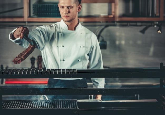 Jonge witte chef-kok in schort die zich dichtbij de koperslager met kolen bevindt. man koken biefstuk in het interieur van de moderne professionele keuken