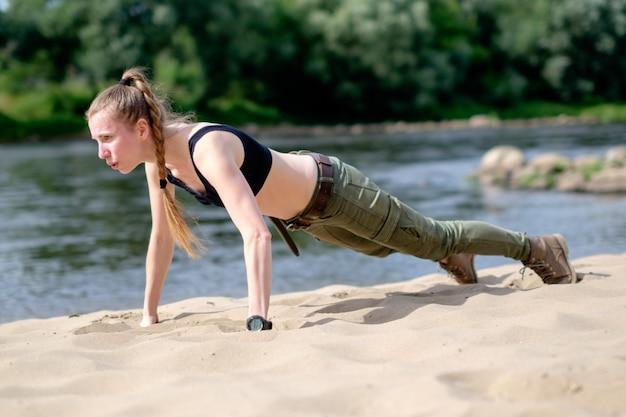 Jonge witte magere roodharige vrouw met vlecht, weared in militaire outfit, doet push ups een zandige oever van de rivier.