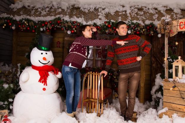 Jonge witte paar in trendy wintermode in de buurt van indoor witte sneeuwpop kijken naar juiste frame in het huis met veel aantrekkelijke kerstversiering.
