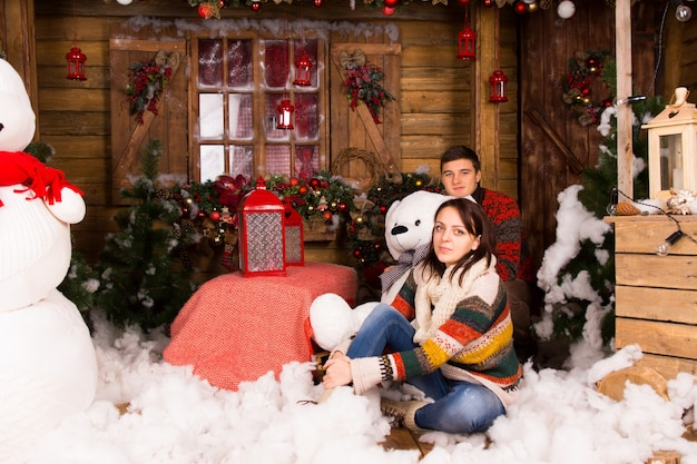 Jonge witte partners in trendy winteroutfits, met grote beer-pop, zittend op een met kerst versierd huis terwijl ze naar de camera kijken.