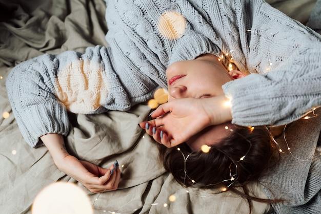Jonge witte vrouw die in bed met rond lichten van feekerstmis en bokeh liggen, ondiepe selectieve nadruk