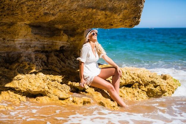 Jonge wo man in witte jurk zittend op de rots op het strand