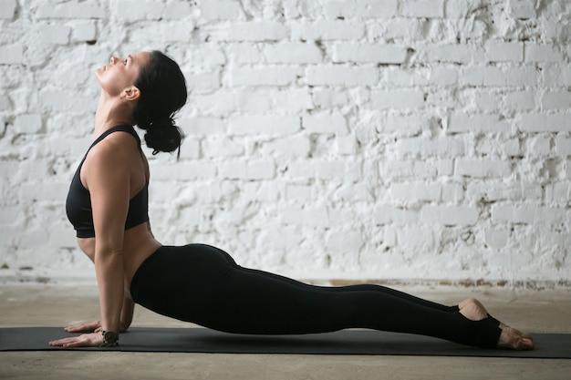Jonge yogi aantrekkelijke vrouw in opwaartse hond staan, studio