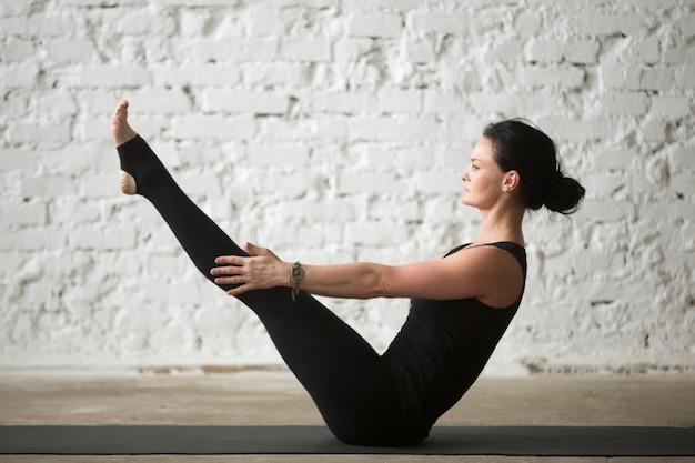 Jonge yogi aantrekkelijke vrouw in paripurna navasana poseren, witte baas