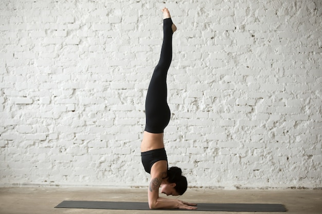 Jonge yogi aantrekkelijke vrouw in pincha mayurasana poseren, loft terug
