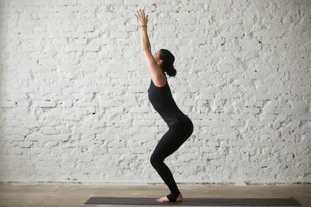 Jonge yogi aantrekkelijke vrouw in stoel poseren, witte loft achtergrond