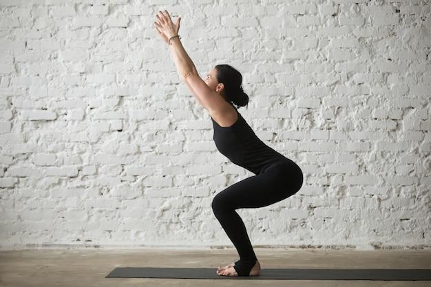 Jonge yogi aantrekkelijke vrouw in utkatasana poseren, witte zolder backg
