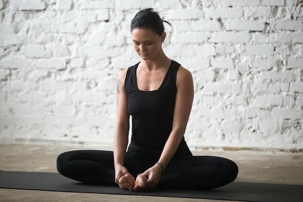 Jonge yogi aantrekkelijke vrouw in vlinder poseren, witte loft achtergronden