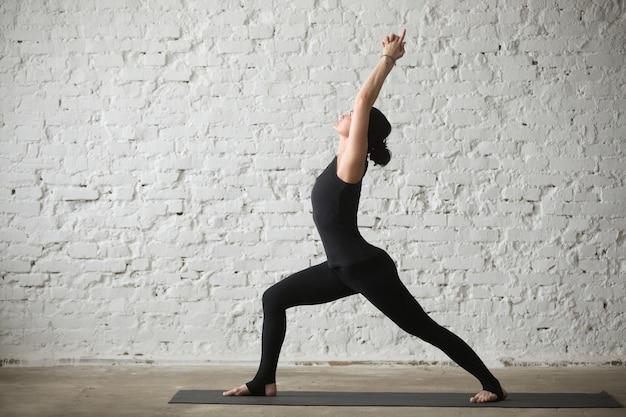Jonge yogi aantrekkelijke vrouw in warrior een stelt, loft achtergrond
