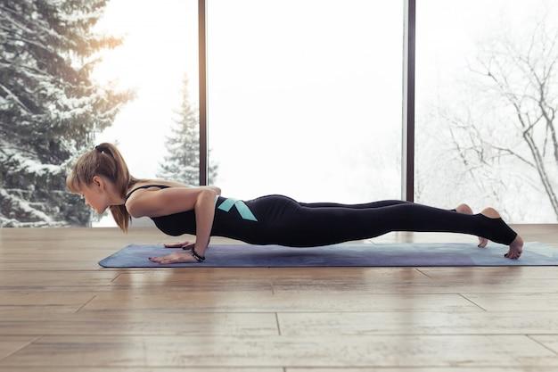 Jonge yogi-vrouw beoefent asana chaturanga