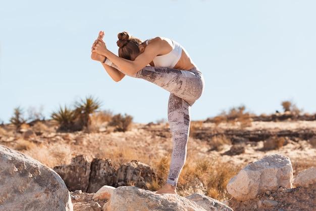 Jonge yogivrouw het praktizeren yoga in woestijn vóór een zonsondergang