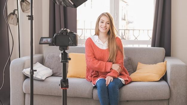 Jonge youtuber of blogger-vrouw die inhoud voor sociale media maakt terwijl ze thuis een video maakt