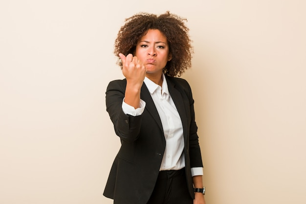 Jonge zakelijke afrikaanse amerikaanse vrouw die vuist toont aan camera, agressieve gelaatsuitdrukking.