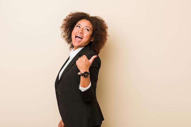 Jonge zakelijke afrikaanse amerikaanse vrouw wijst met duimvinger weg, lachend en zorgeloos.