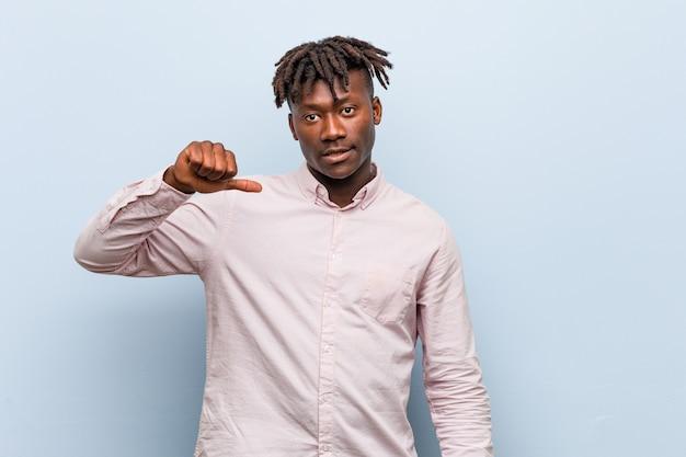 Jonge zakelijke afrikaanse zwarte man met een afkeer gebaar, duimen naar beneden. onenigheid .
