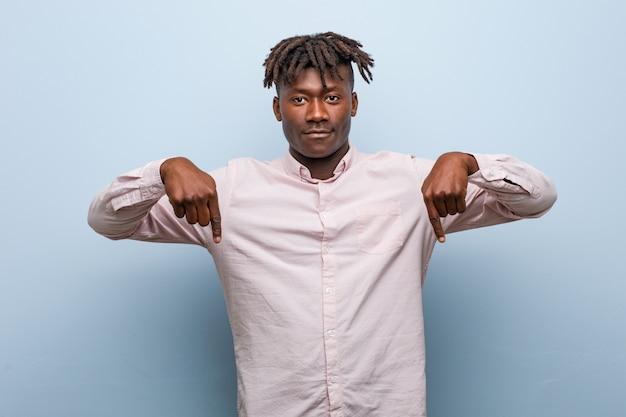Jonge zakelijke afrikaanse zwarte man wijst naar beneden met vingers, positief gevoel.