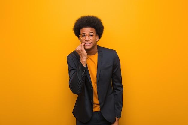 Jonge zakelijke afro-amerikaanse man over een oranje muur nagels te bijten, nerveus en erg angstig