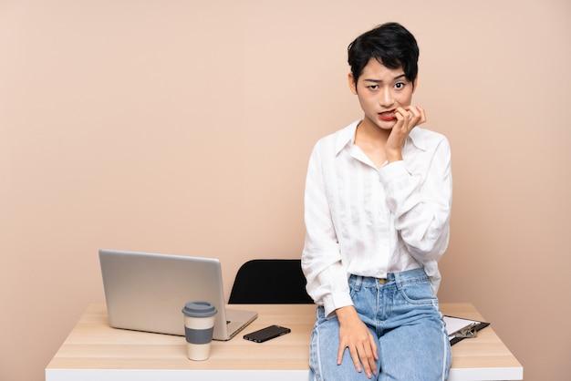 Jonge zakelijke aziatische vrouw op haar werkplek nerveus en bang