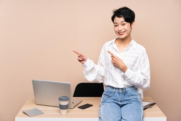 Jonge zakelijke aziatische vrouw op haar werkplek wijzende vinger naar de kant