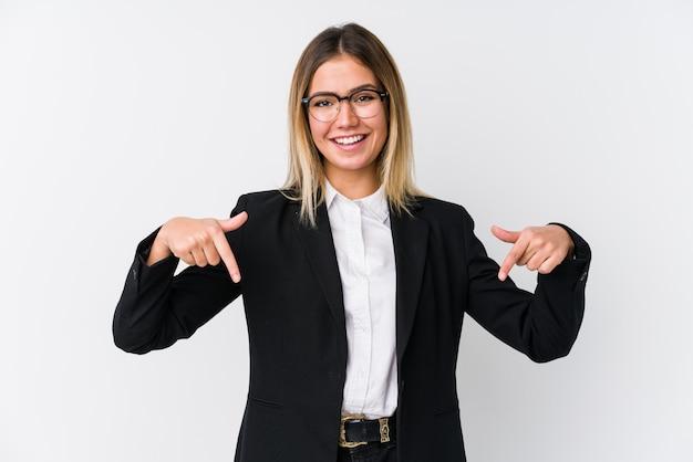 Jonge zakelijke blanke vrouw wijst naar beneden met vingers, positief gevoel.